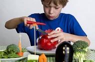 Jongen snijdt met mesje in groente