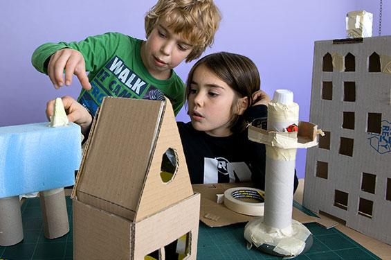 kinderen knutselen met kartonnen dozen